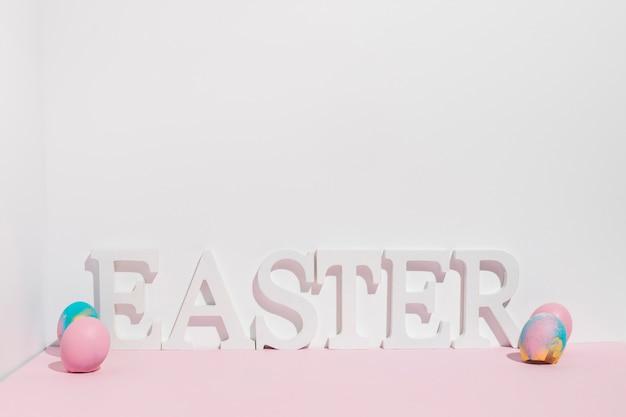 Ostern-aufschrift mit bunten eiern auf tabelle