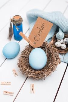 Ostern-aufschrift mit hellem ei im nest