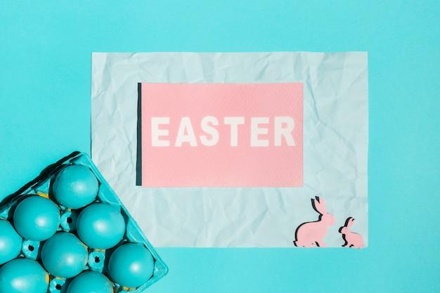 Ostern-aufschrift mit hellen eiern im gestell und in den hölzernen kaninchen