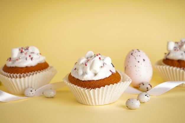 Ostern cupcakes und ostereier auf gelbem hintergrund