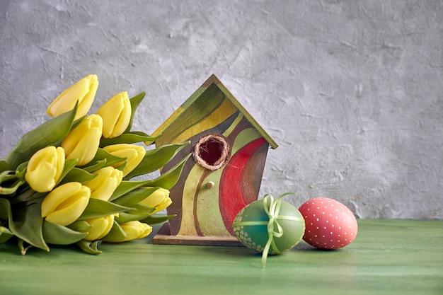 Ostern dekorationen auf grauem beton. gelbe tulpen, vogelhäuschen und bemalte ostereier