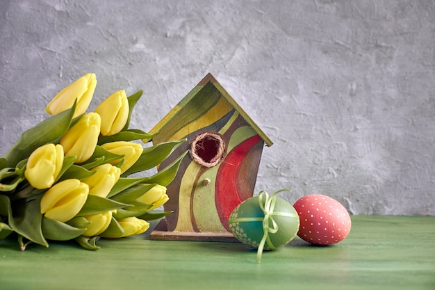 Ostern-dekorationen auf grauem konkretem hintergrund. gelbe tulpen, vogelhäuschen und bemalte ostereier