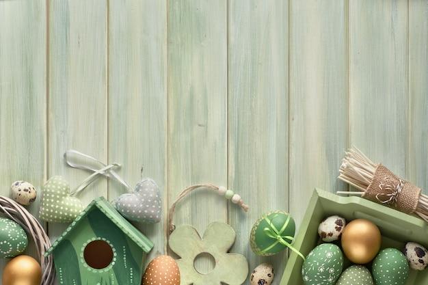 Ostern-ebene legen auf grüne hölzerne planken mit frühjahrdekorationen, eiern und nistkasten, kopieraum