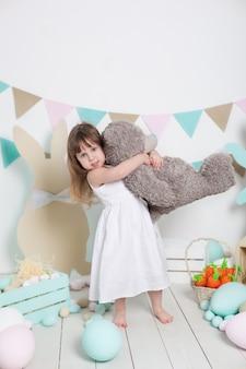 Ostern! ein schönes kleines mädchen in einem weißen kleid umarmt einen großen teddybären. viele verschiedenen bunten ostereier. muttertag und frühling, familienferien. ostern innenraum. kind spielt mit einem spielzeug