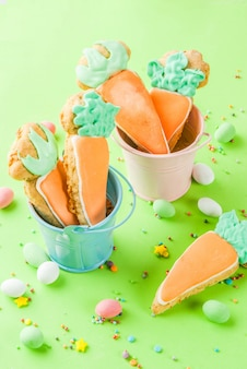 Ostern-feiertagskonzept, süße plätzchen in der form von karotten, mit bonbon besprüht und ei-süßigkeiten, draufsicht des hellgrünen hintergrundkopienraumes, grußkartenhintergrund