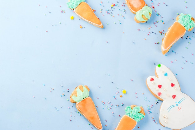 Ostern-feiertagskonzept, süße plätzchen in der form von karotten, osterhase, mit bonbon besprüht, hellblaue draufsicht des hintergrundkopienraumes, grußkartenhintergrund