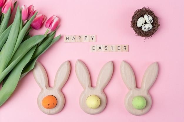 Ostern-feiertagsrosahintergrund mit farbigen eiern in den häschenohren formte eierbecher, rosa blumentulpe