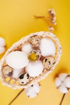 Ostern flach lag zusammensetzung mit baumwollblumen und ostereiern in einem kleinen korb auf gelbem hintergrund. frohe osterferien, platz kopieren.