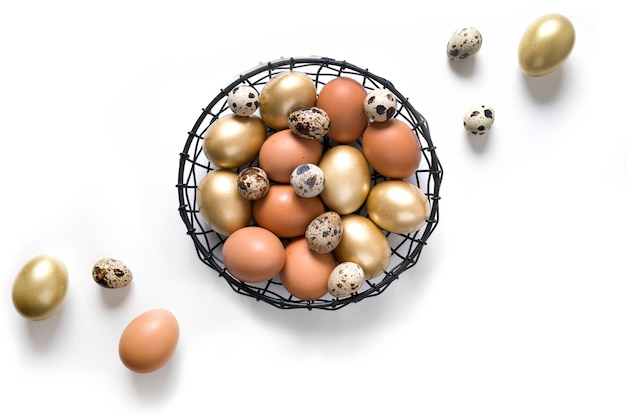 Ostern golden, wachtel, hühnereier in der schüssel auf weiß. sicht von oben. minimale zusammensetzung.