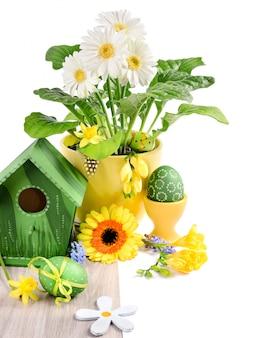 Ostern-grenze mit frühlingsblumen und handgemachten dekorationen auf holz
