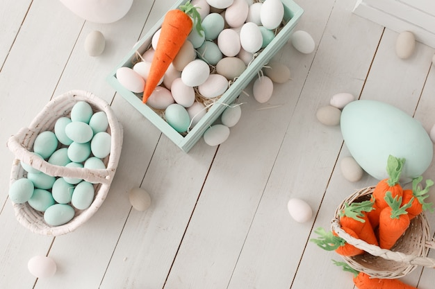 Ostern-hintergrund mit bunten eiern und gelb-orangeen karotten über weißem holz.