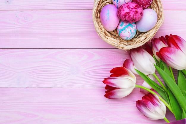 Ostern-hintergrund mit bunten eiern und tulpen über rosa holz. draufsicht mit kopienraum