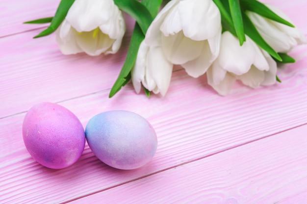 Ostern-hintergrund mit bunten eiern und tulpen über rosa holz.