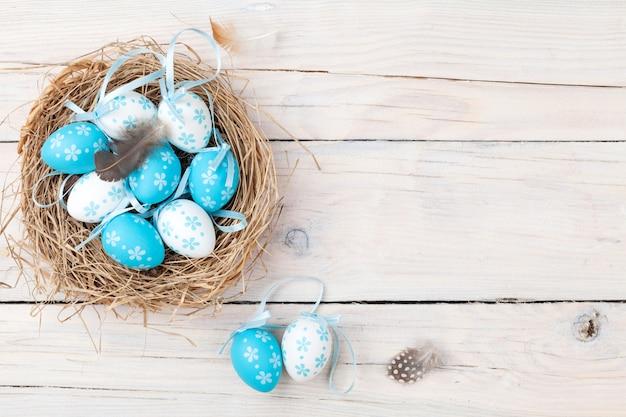 Ostern-hintergrund mit den blauen und weißen eiern im nest