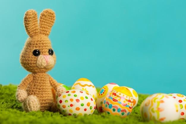 Ostern-hintergrund mit gebrochenen eiern, grünem gras, blauem himmel und osterhasen