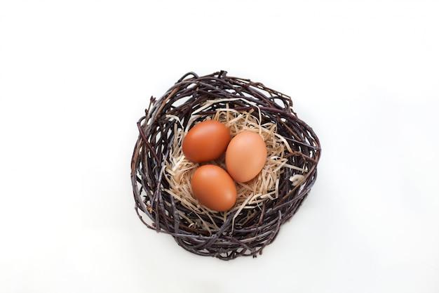 Ostern! hühnereien in einem nest mit niederlassungen, landwirtschaft. ostereier auf dem tisch im nest.