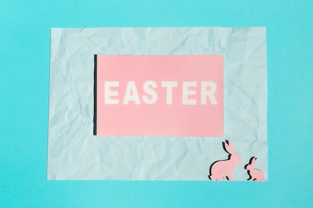 Ostern-inschrift auf papier mit hölzernen kaninchen
