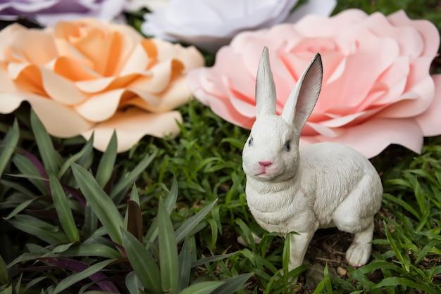 Ostern-kaninchen und fälschung verzierten blumen im garten