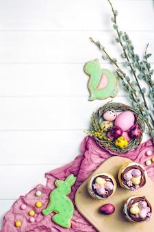 Ostern-kleine kuchen, gemalte eier und blühende pussyweidenbrunchs auf weißem hölzernem hintergrund