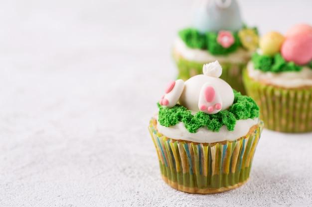 Ostern-kleine kuchen mit lustigem häschen und gras auf weißem hintergrund. ostern-feiertagskonzept