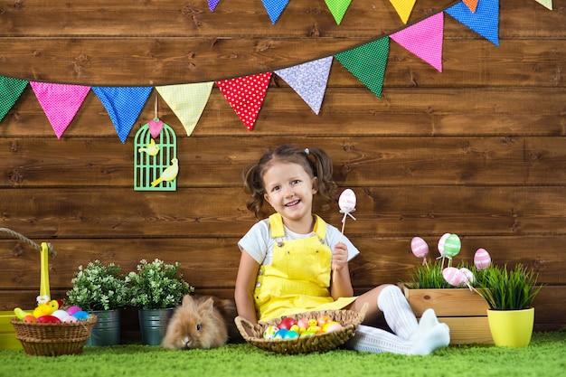 Ostern. kleines mädchen in osterhasenohren mit farbigen eiern auf holzuntergrund