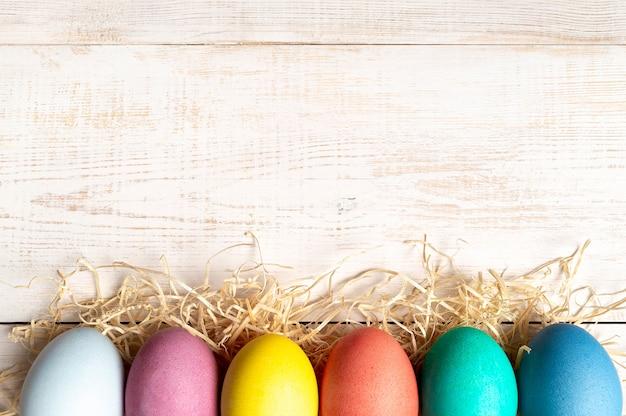 Ostern-konzept. bunte eier auf weißem hölzernem hintergrund mit kopienraum für text. ansicht von oben nach unten oder flach legen
