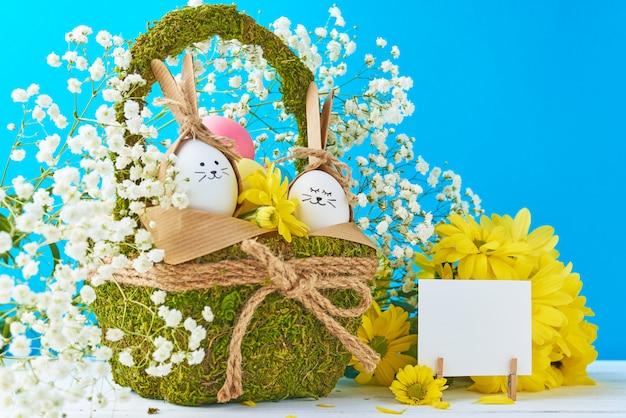 Ostern-konzept eier im korb verziert mit blumen auf einem blauen hintergrund