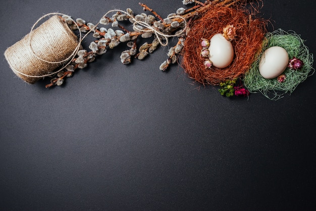 Ostern-konzept, eier, zweige der pussyweide auf schwarzem hintergrund.
