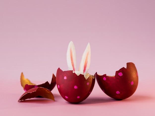 Ostern-konzept. farbige eier auf rosa hintergrund, osterhasenverstecken