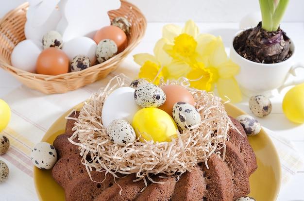 Ostern-kuchen mit gefärbten eiern in einem nest, in narzissen und in einer hyazinthe in einer schale auf einem weißen rustikalen hölzernen hintergrund