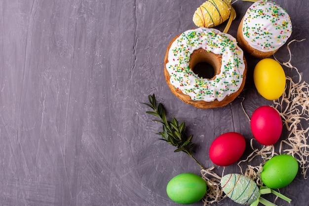 Ostern-kuchen und bunte eier auf einem dunklen hintergrund