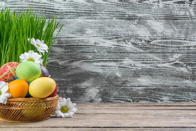 Ostern malte eier und blumen auf rustikalem holztisch