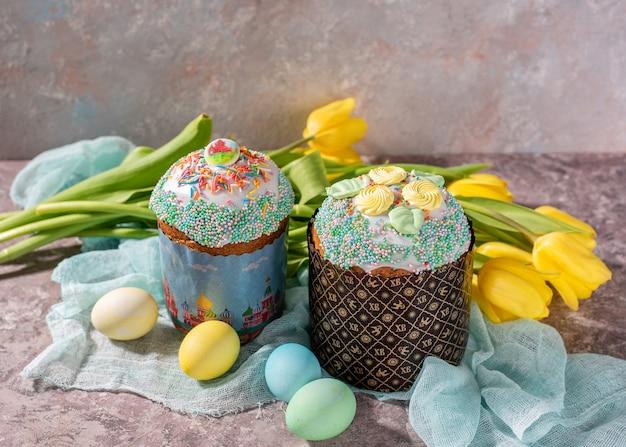 Ostern noch leben. ostern-kuchen, gemalte eier mit tulpen auf einem hölzernen alten rustikalen hintergrund.