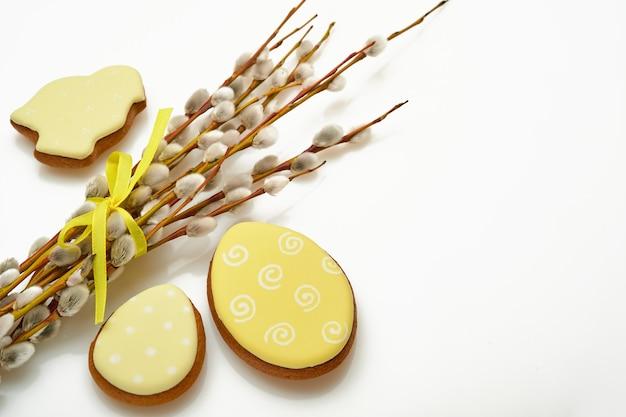 Ostern. pussy weidenzweige gelbes band und ostern lebkuchenhasen, hühner und eier isoliert
