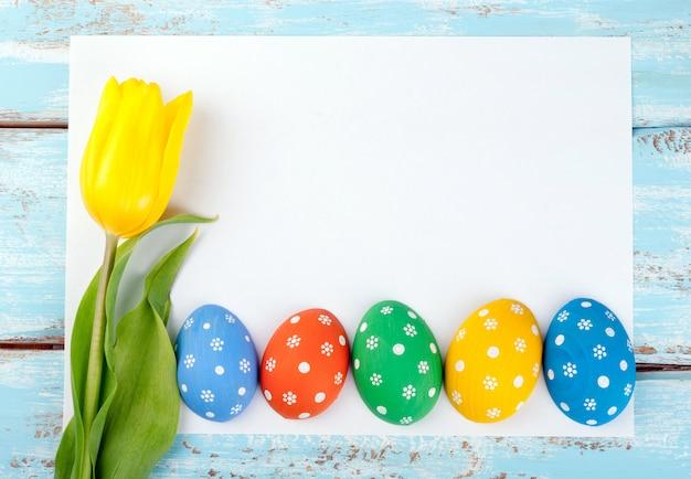 Ostern-rahmenhintergrund mit eiern, tulpenblume und weißem leerem papier für text