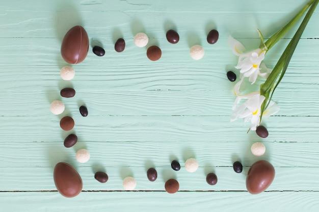 Ostern schokoladeneier und blumen auf grüner holzoberfläche
