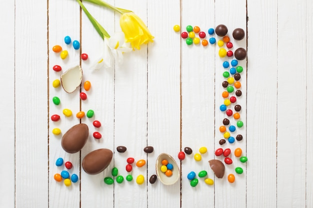 Ostern schokoladeneier und bonbons auf weißer holzoberfläche