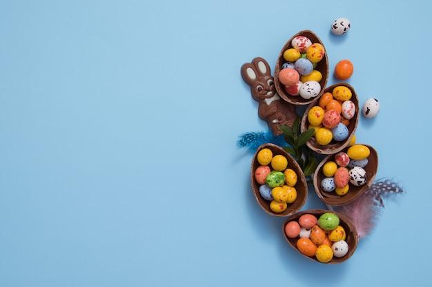 Ostern schokoladeneier und hase auf blauem tisch
