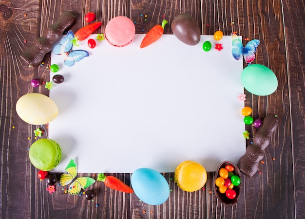 Ostern set rahmen und klares weißes blatt eier, karotten, schokoladenhase, süßigkeiten, makronen. speicherplatz kopieren. draufsicht.