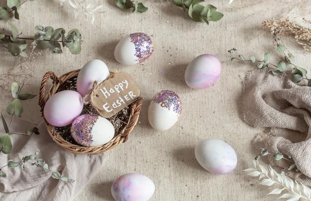 Ostern stillleben mit eiern mit pailletten in einem weidenkorb verziert. glückliches osterkonzept
