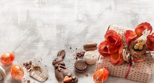 Ostern stillleben mit geschenk und süßigkeiten auf holz.