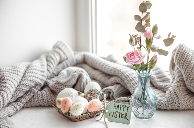 Ostern stillleben mit ostereiern, frischen blumen in einer vase und der aufschrift frohe ostern auf der postkarte.