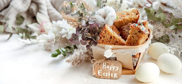 Ostern stillleben mit stücken von festlichem cupcake, eiern und blumen auf einem unscharfen hellen hintergrund. osterferienkonzept.