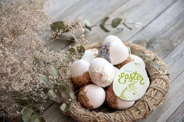 Ostern stillleben mit verzierten ostereiern und dekorativem nest auf einer holzoberfläche mit trockenen zweigen. frohe ostern wünscht konzept.