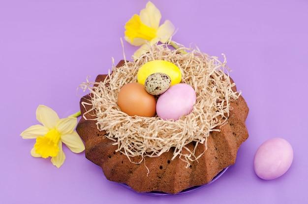 Ostern-stillleben, ostern-kuchen-, hühner- und wachteleier, auf einem violetten hintergrund.