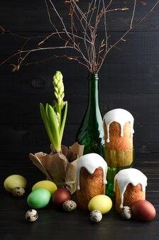 Ostern-stillleben ostern-kuchen und -eier auf einem dunklen, hölzernen hintergrund.