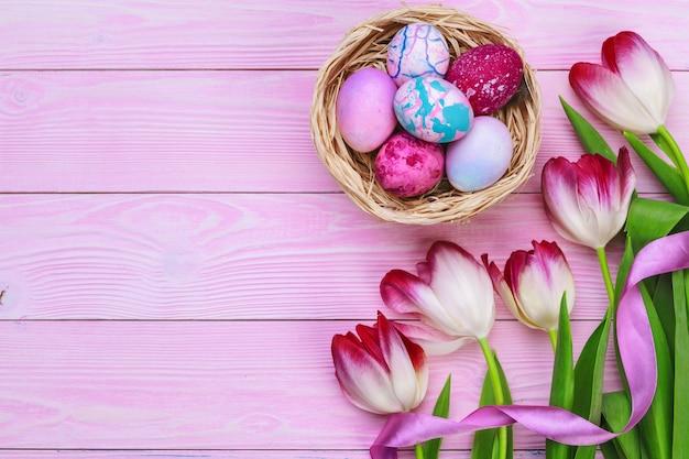 Ostern-thema mit bunten eiern und tulpen über rosa holz. draufsicht mit kopienraum