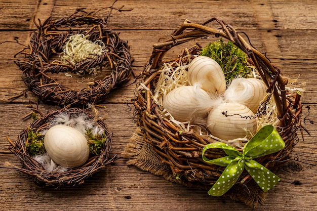 Ostern weidenkorb, vogelnest, kranz. null abfall, diy-konzept. holzeier, späne, satinschleife. hintergrund der alten bretter
