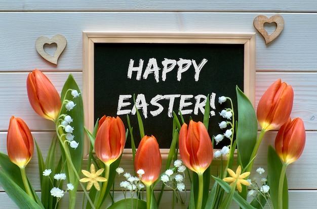 Ostern-zusammensetzung mit der tafel gestaltet mit frühlingsblumen, tulpen und maiglöckchen, text