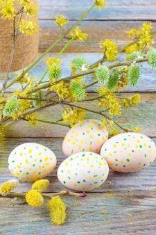 Ostern-zusammensetzung von blühenden weidenzweigen, von hartriegeln und von ostereiern mit einem muster von gelben und grünen punkten auf einer hölzernen retro- hintergrundraumnahaufnahme